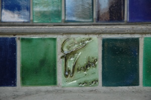 Close up of paints tiles on a staircase that are green and blue. The artists name Catherine winship is carved into one of the tiles.
