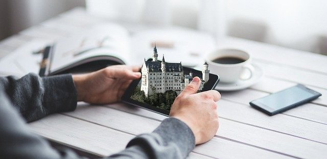 Close up of two hands holding a phone and a 3D castle is popping out of the phone screen